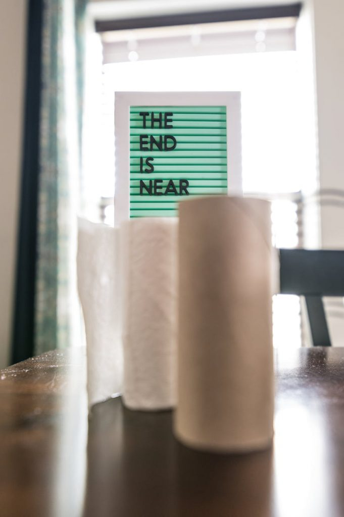 rolls of paper towels on table near board with lettering